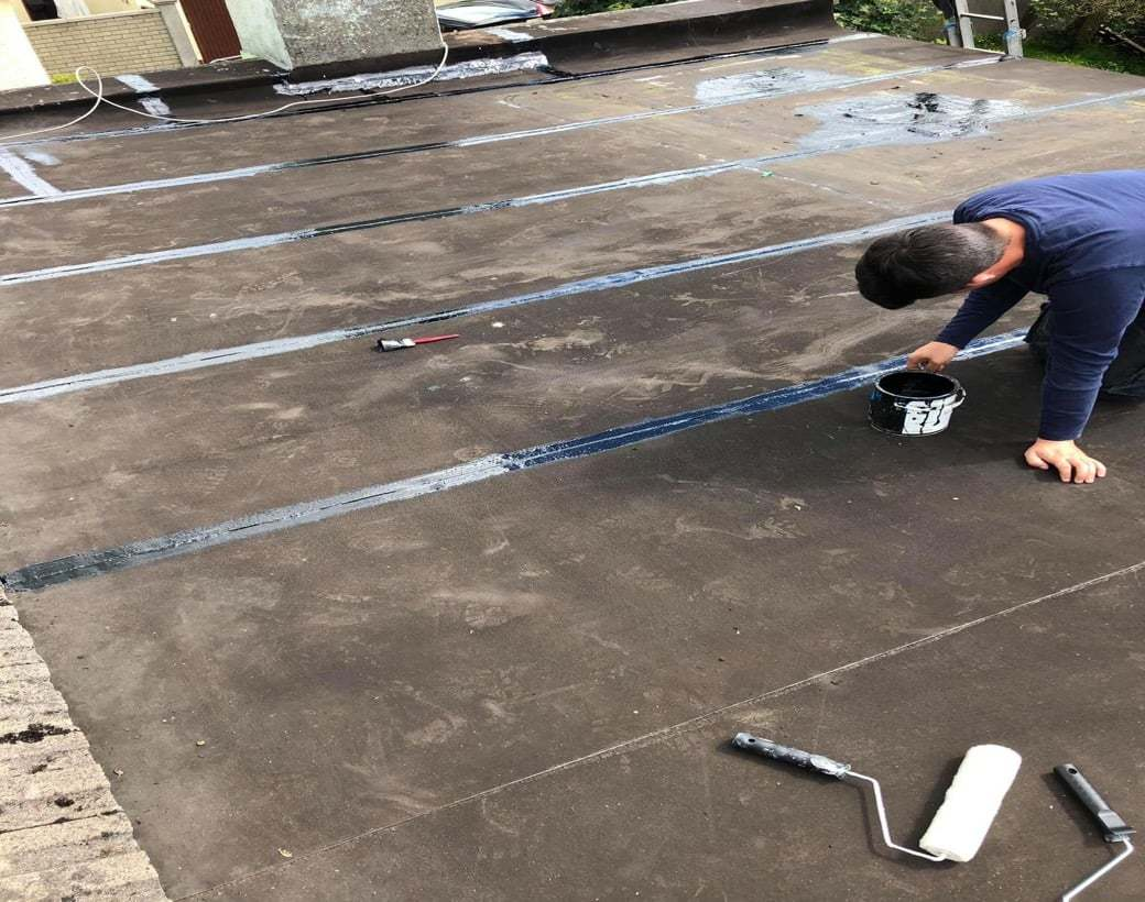 Repairing Flat Roof apply Adhesive